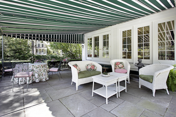 Backyard deck with patio furniture and white and green awning.