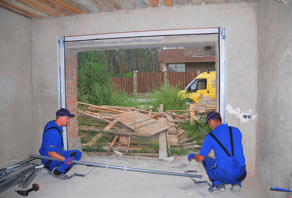 Workers repairing a garage door.