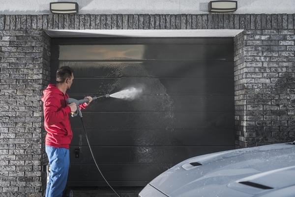 Man power washing his garage door.