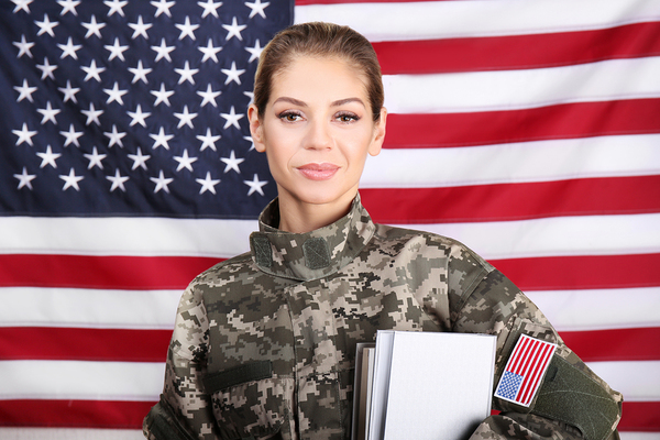 woman in the military hold papers and an american flag in the background