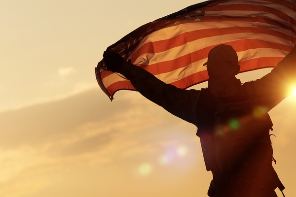 man holding american flag with a sunset in the background