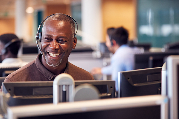 Smiling man talking with a headset at a computer.