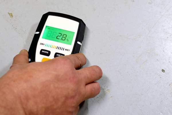 Man using a moisture meter on a wall