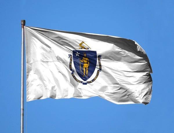 Massachusetts state flag flying with a blue sky in the background.