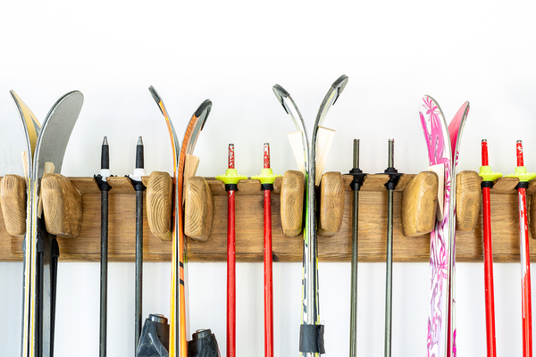 Snow skis and poles on a rack.