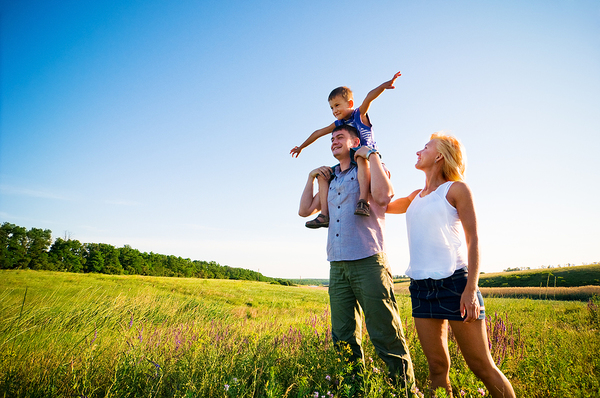Family outside in a green pasture.