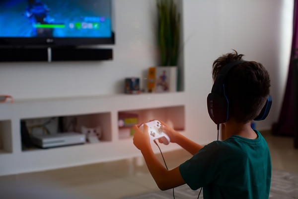 Young teen playing a video game.