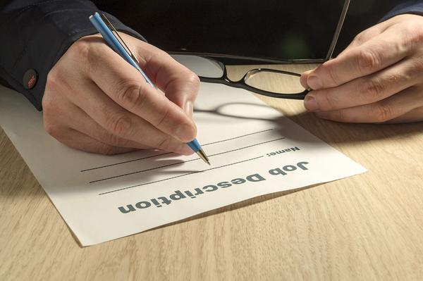 Person filling out a document labeled job description.