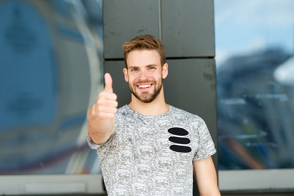 Happy man standing against a stone wall with thumbs up.