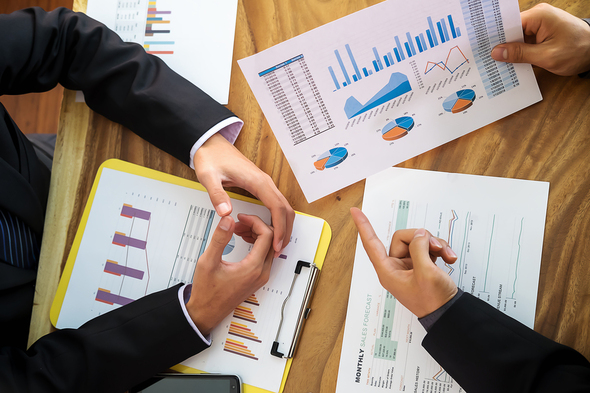 Two people discussing documents with charts and graphs.