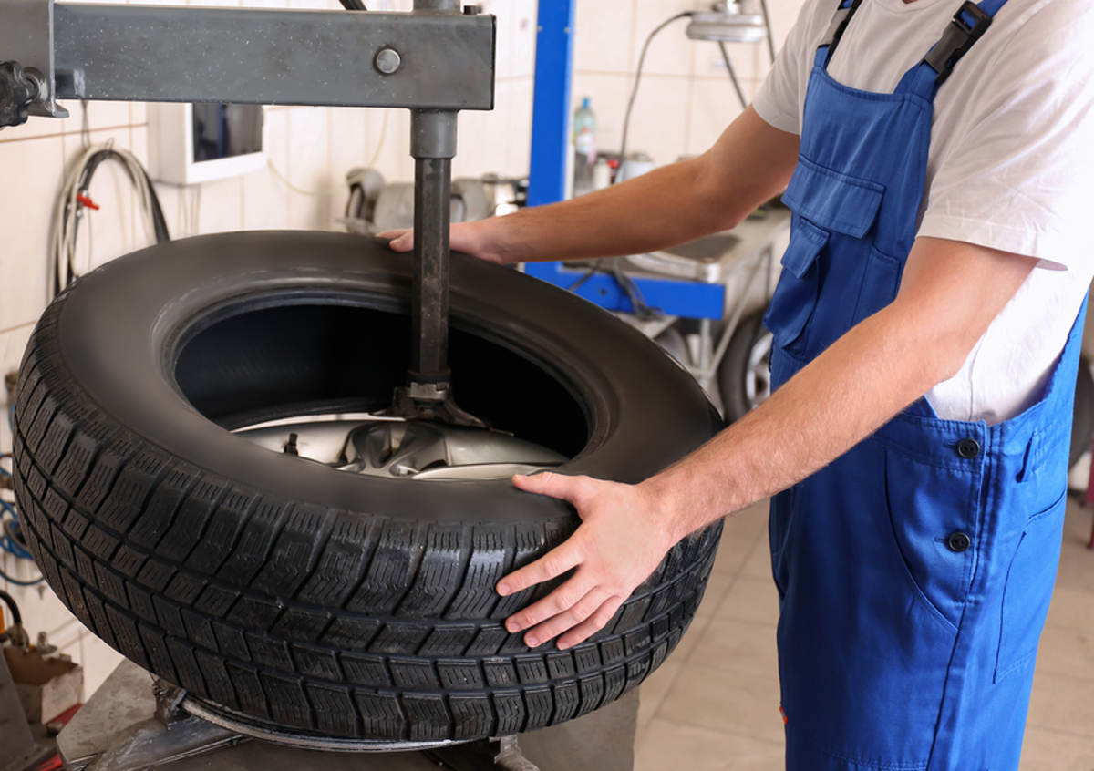 Mechanic placing a tire on a new rim.