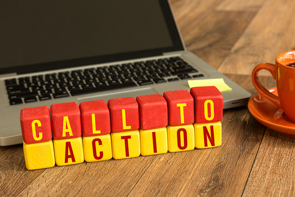 "Laptop computer with wooden blocks spelling ""call to action."" Personalized calls-to-action increase sales conversions, and they should be segmented based on the buyers journey."