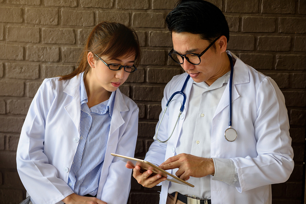 Two physicians discussing a healthcare marketing plan while looking at data in a tablet.