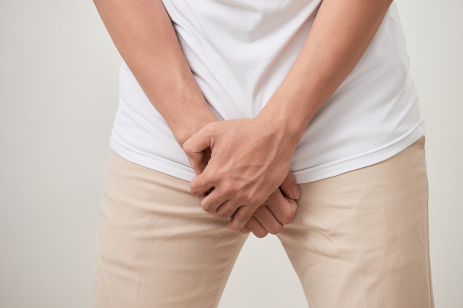 Person crossing their hands over their pant front.