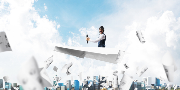 Person flying in the air on a paper airplane.