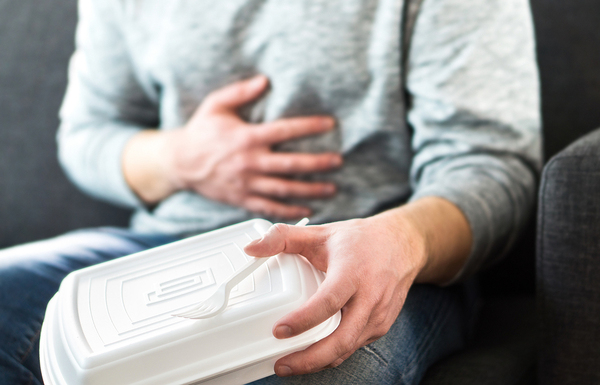 Person holding their stomach and styrofoam food container.