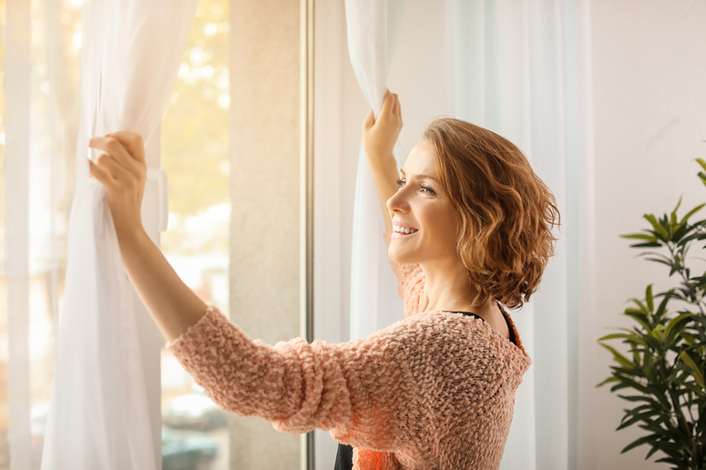 Woman pushing drapes aside on a window.