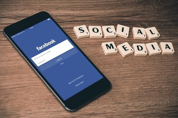 (Table with smartphone opened to Facebook and blocks spelling out social media.) There are many different channels for real-time marketing, but social media is one of the best thanks to its immediacy.
