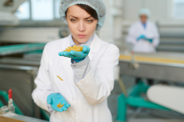 Woman inspecting food item in a manufacturing plant.