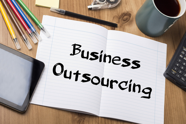 desk with a piece of paper on it saying business outsourcing