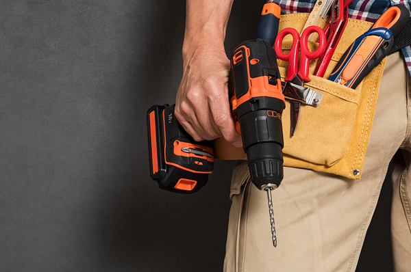 Man wearing a tool belt and holding an electric screwdriver