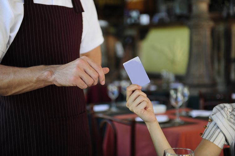 Woman paying for her meal with a credit card.