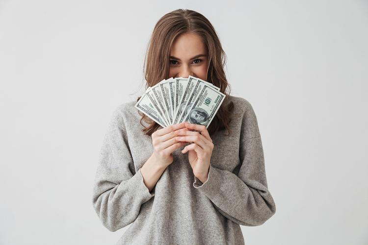 Woman holding a fan of paper money.