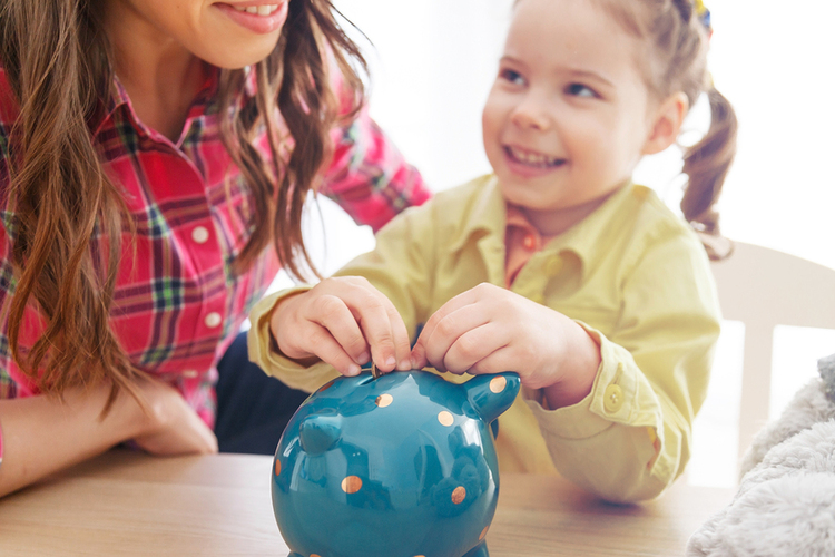 Young girl placing money in her piggy bank.