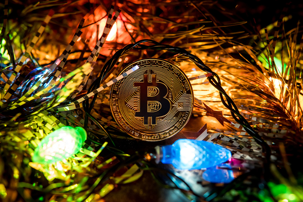 Gold coin with a bitcoin symbol and holiday lights.