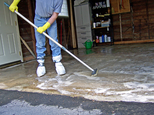 Person cleaning the floor of their garage.