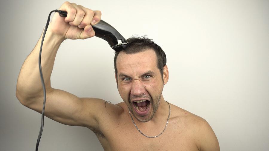 Man using a hair clipper on his hair.