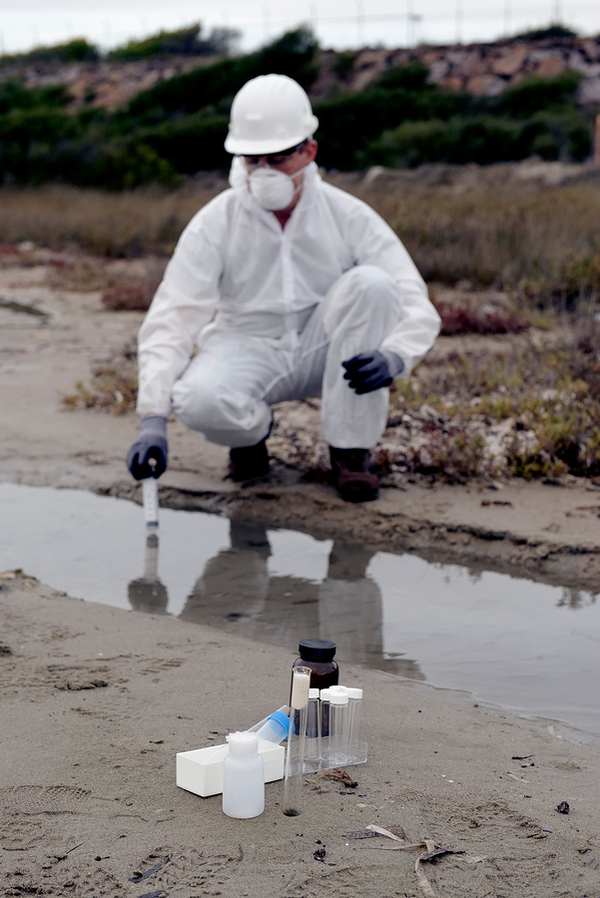 Man in a white jumpsuit, mask and hat taking a water sample.