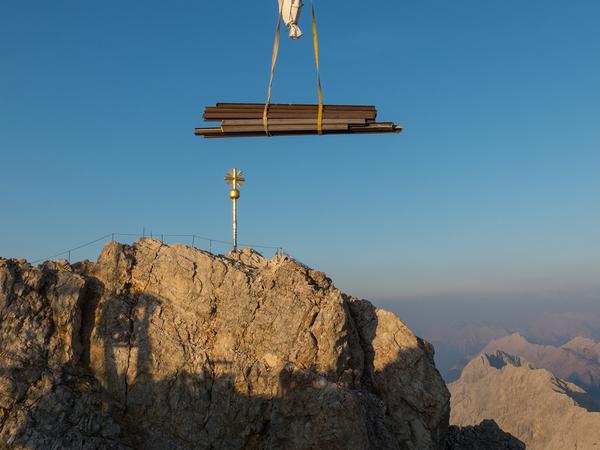 Crane hoisting large iron bars.