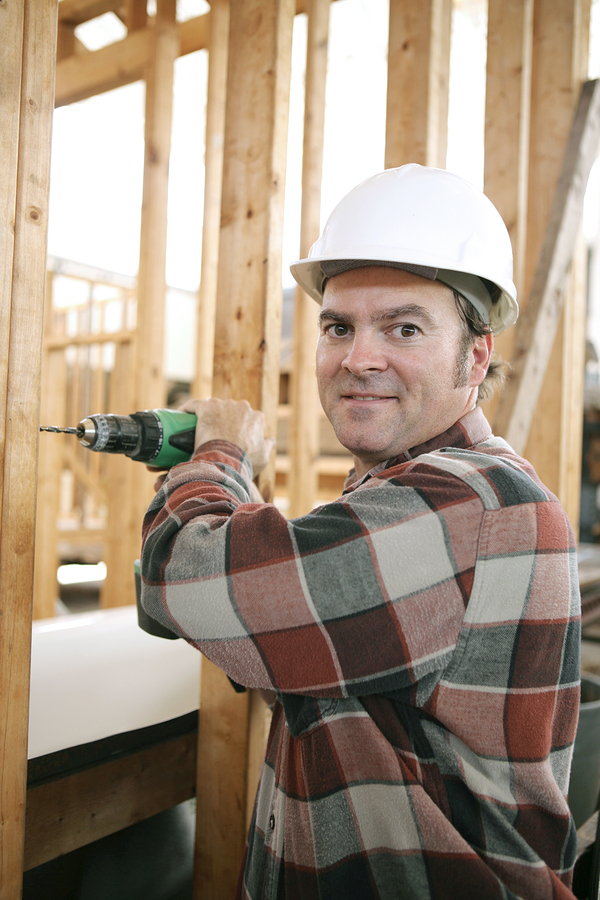 Construction worker with a hard hat and drill.