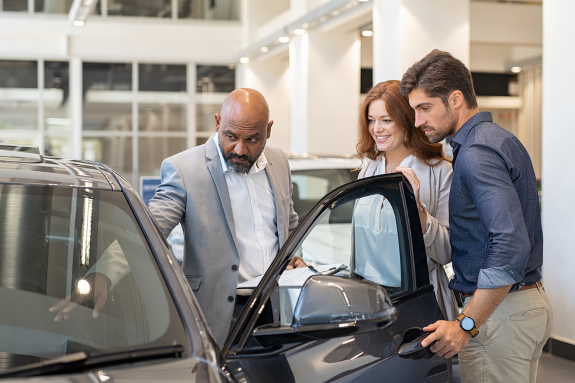 Couple looking at a new car in a dealership.