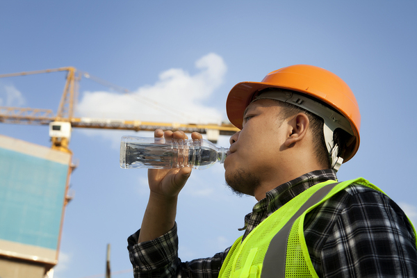 Construction worker drinking a bottle of water.