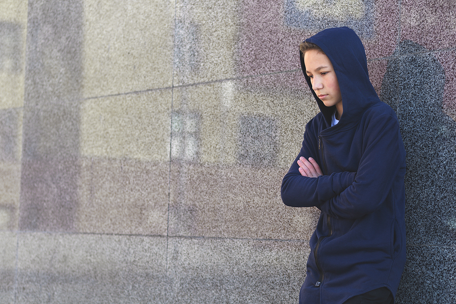 Teen boy standing against a wall wearing a dark blue hoodie.