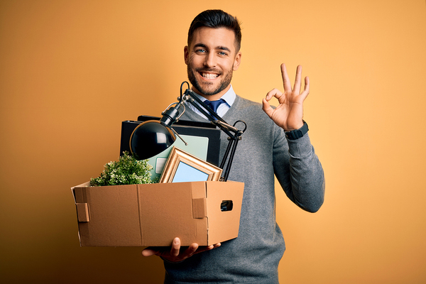 Man holding a cardboard box filled with desk items.