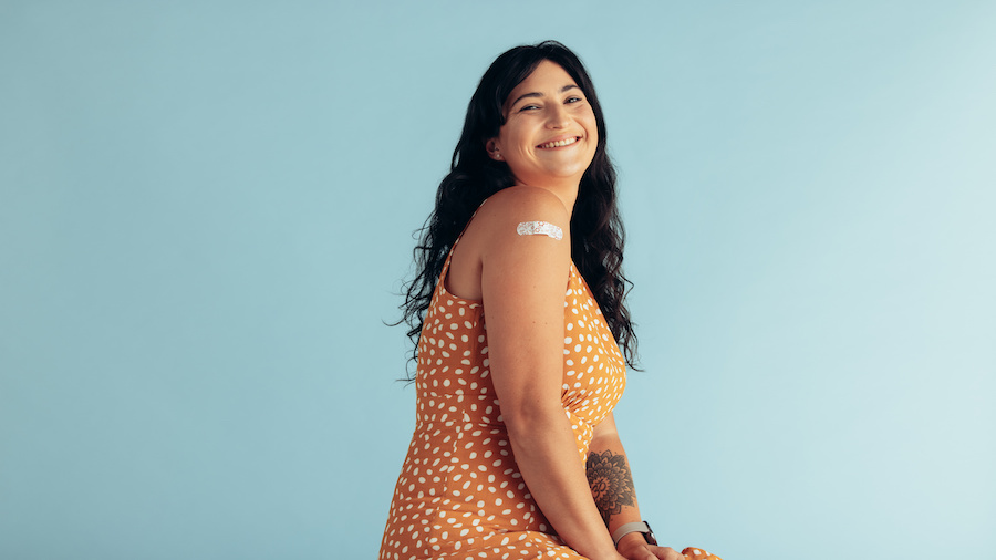 Smiling woman with a band-aid on her arm.