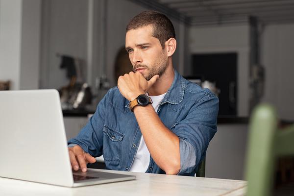 Man looking at his laptop screen.