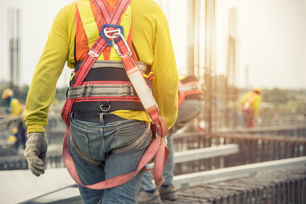 Construction worker with yellow shire and orange harness.
