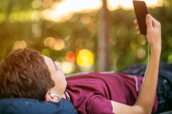 Teen lying down looking at his phone screen.