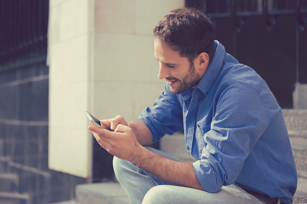 Man sitting on steps using his mobile phone.