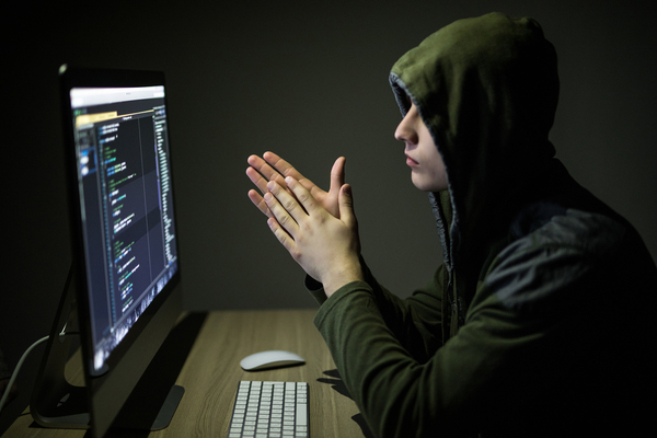 Person in a hoodie working on a desktop computer.