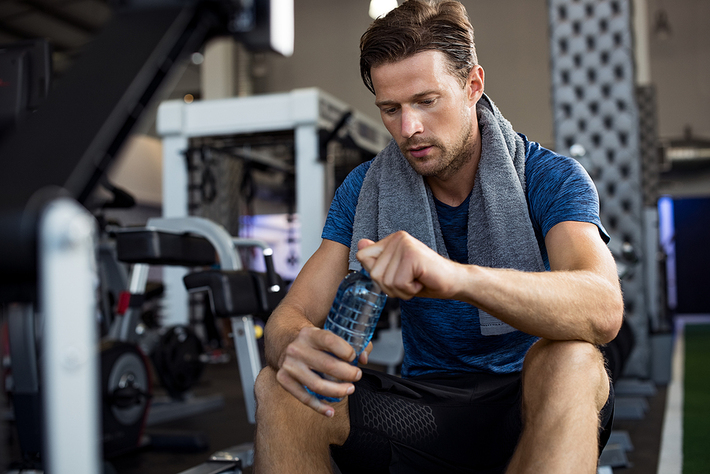 Man sitting in a gym opening a water bottle.