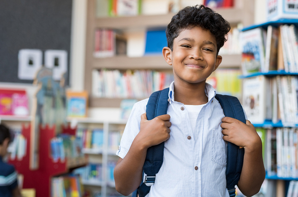 Young boy with a backpack in a book store smiling.
