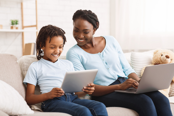 Parent and child sitting together using computers.