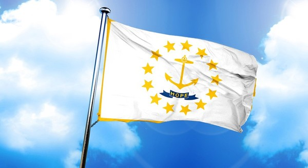 Rhode Island state flag flying with blue sky in the background.