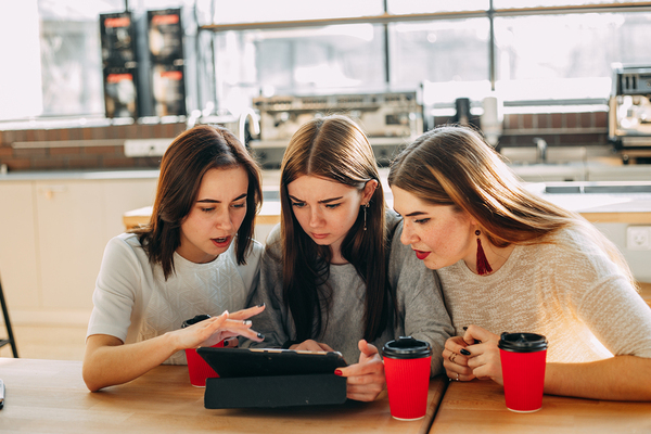 Group of teens looking at a tablet together.