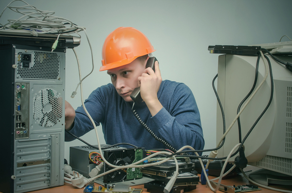 Man working on a computer while speaking on the phone.